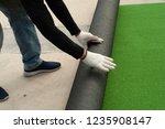 man worker unroll roll of... | Shutterstock . vector #1235908147