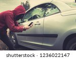 Side view of young criminal in black balaclava and hoodie holding smartphone and trying to interact with car by mobile application. Unknown person tries to get access to the vehicle using app. Fraud - stock photo