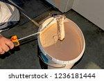a painter dips a paint roller... | Shutterstock . vector #1236181444