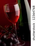 a glass and  a bottle of red wine and grape - stock photo