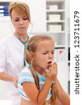 Coughing little girl on health checkup at the doctor - stock photo
