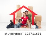 Happy family in a new home concept - sitting with cardboard boxes - stock photo