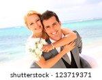 groom holding bride on his back   Shutterstock . vector #123719371