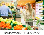 Woman holding an apple in a supermarket - stock photo