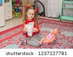 a little girl in red is played...   Shutterstock . vector #1237227781