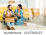 serious couple putting books in ... | Shutterstock . vector #1237263127