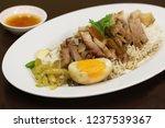 Small photo of Kho Kha Moo.Rice with pork leg,Thai food on wood table.
