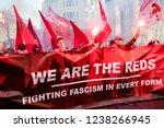London, United Kingdom, November 17th 2018:- Reds setting off flares at the Stand Up To Racism march through central London from the BBC to near Downing Street in Whitehall - stock photo