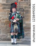 Small photo of Edinburgh, Scotland - May 24, 2018: Man in traditional Scottish clothing playing bagpipe at the Royal Mile in Edinburgh
