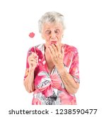Small photo of Excited old woman holding amiss photo booth prop with her eyes closed against a white background