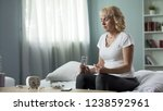 sick blond lady sitting on bed... | Shutterstock . vector #1238592961