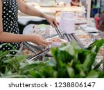 Small photo of Woman's hands taking pork from tray at a buffet hotpot ( Moo Joom ) restaurant with a defocus vegetables in the foreground