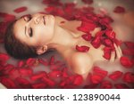 Stock photo attractive girl in bath with milk and rose petals spa treatments for skin rejuvenation alluring 123890044