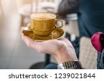 a cup of coffee in the hand of... | Shutterstock . vector #1239021844