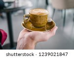 a cup of coffee in the hand of... | Shutterstock . vector #1239021847
