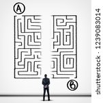 Small photo of Thoughtful businessman solving a maze using a shortcut. Maze drawn on a white wall. Point a to point b.
