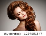 Stock photo beauty fashion model with long shiny hair waves curls volume hairstyle hair salon updo woman 1239651547