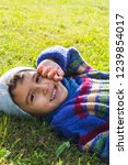 cheerful boy lying on the grass ... | Shutterstock . vector #1239854017