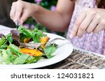 Pair of woman's hands holding cutlery eating a fresh healthy raw spring salad with butternut pumpkin squash at a casual outdoor dining meal location - stock photo