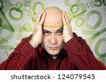 Problem with mortgage rates. Man having headache because of mortgage rates, computer generated percentage signs fly around his head. - stock photo