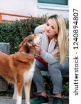 Stock photo beautiful girl with his shetland sheepdog dog sitting and posing in front of camera on wooden bench 1240894807