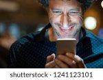 smiling man using smart phone... | Shutterstock . vector #1241123101