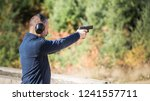 adult male with a handgun at... | Shutterstock . vector #1241557711