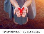 red ribbon in women hands for... | Shutterstock . vector #1241562187