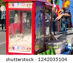 a young man sells popcorn and... | Shutterstock . vector #1242035104