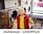 a little boy loads clothes into ... | Shutterstock . vector #1242099124