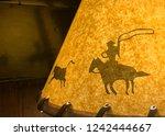 cowboy roping a calf depicted... | Shutterstock . vector #1242444667