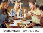 friends having dinner at... | Shutterstock . vector #1242477157