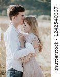 young couple kissing in a field | Shutterstock . vector #1242540337