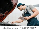 Small photo of side view of auto mechanic with tablet checking car cowl at mechanic shop