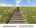 wooden stairs upon green hill... | Shutterstock . vector #1243107334