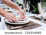 Pair of hands making final adjustments to a napkin for a simple rustic country style table setting, a party gathering in a casual outdoor garden setting - stock photo
