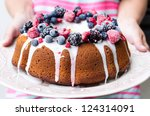 Woman hands holding vanilla bundt cake dessert with icing glaze topped with mixed berries raspberry blueberry blackberry - stock photo