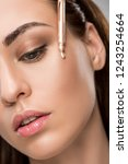 Stock photo attractive girl applying highlighter or bronzer with pipette 1243254664