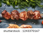 Small photo of Deep Grilled Golden Lamb Kebab or Barbecue Shashlik on a Skewer with Spices Top View. Macro Photo of Skewered Grilled Cubes of Mutton Meat with Selective Focus on Black Background with Fresh Greens