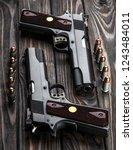 black pistol and cartridges on... | Shutterstock . vector #1243484011