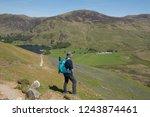 female walker admiring the view ... | Shutterstock . vector #1243874461