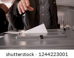 hand of a person casting a vote ... | Shutterstock . vector #1244223001