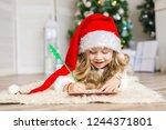 Little Girl In Santa Hat Writes ...