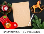 New Year or Christmas mockup. Template for letter to Santa, list of plans and goals for New Year, wishlist near fir branches, Christmas socks, toy horse on black background top view