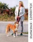 Stock photo woman in walk with his shetland sheepdog dog on leash dog walker standing posing in front of 1245007414