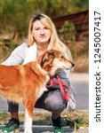 Stock photo pretty girl with his shetland sheepdog dog at nature park outdoor is standing and posing in front 1245007417