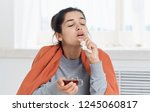 ailing woman with a cup of tea... | Shutterstock . vector #1245060817