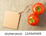 two tomatoes with cardboard tag on sacking - stock photo