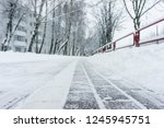 Winter frozen pavement walkway under snow in a park. Pavement walkway perspective view abstract winter background