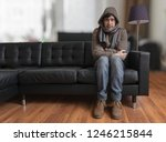 Young Man Sitting On Couch Is...